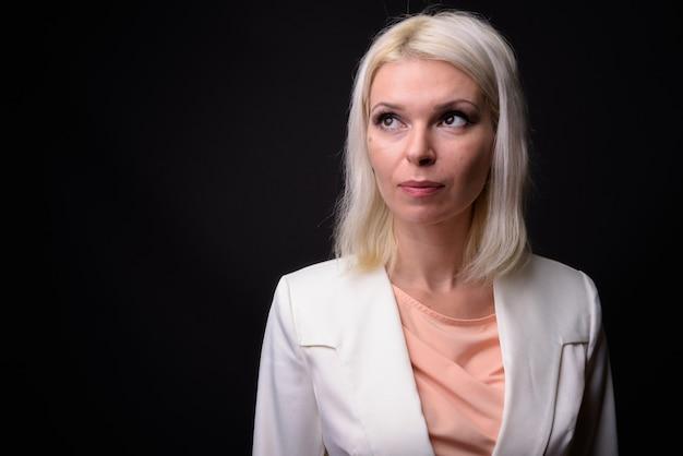 ブロンドの髪の思考と計画と美しい女性実業家