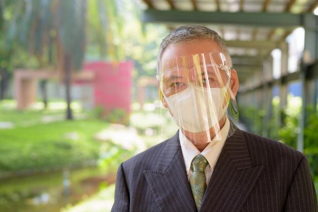 公園でマスクと顔のシールドを身に着けている成熟した日本のビジネスマン