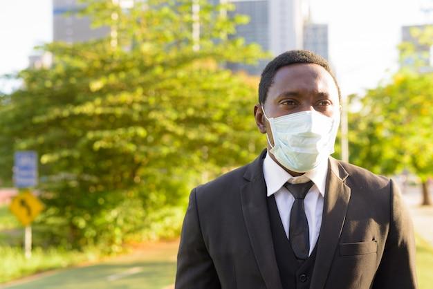 Лицо африканского бизнесмена с маской мышления в парке в городе