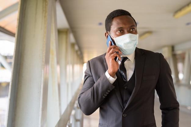 Портрет африканского бизнесмена с маской, разговаривает по телефону на пешеходном мосту