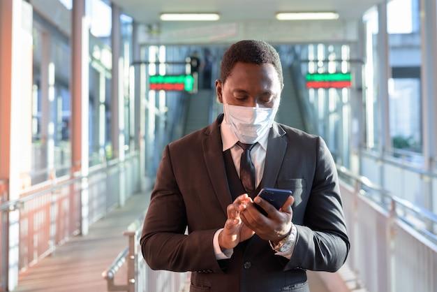 Портрет африканского бизнесмена с маской с помощью телефона на вокзале на открытом воздухе