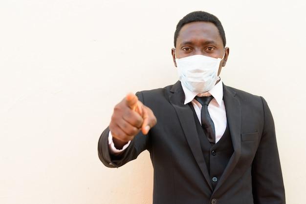 Подчеркнул африканского бизнесмена с маской, указывая на камеру на белом фоне
