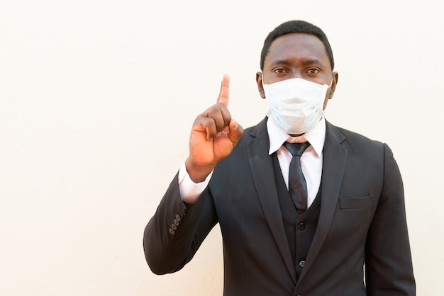 Африканский бизнесмен с маской на белом фоне