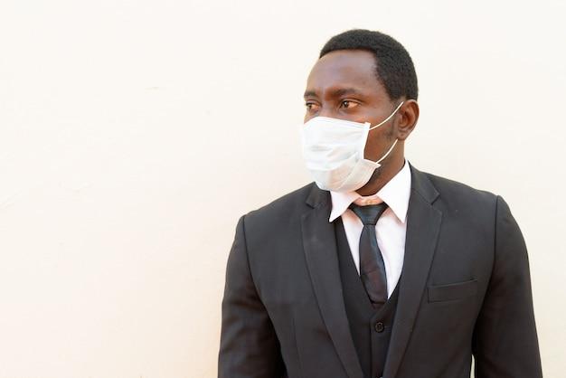 Портрет африканского бизнесмена с маской думать на белом фоне