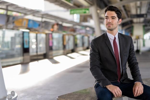 駅に座っている若いハンサムなビジネスマンの肖像画