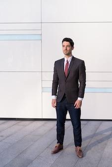 市でスーツを着ている若いハンサムなビジネスマンの肖像画