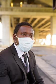 Африканский бизнесмен с маской думать и ждать на автобусной остановке