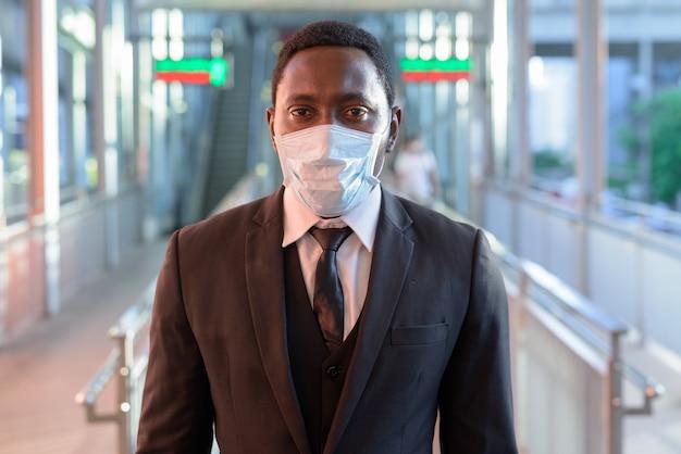 Лицо маски африканского бизнесмена носить на вокзале на открытом воздухе