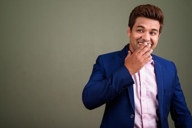 色付きの背景に対してスーツを着ているインドのビジネスマンのスタジオ撮影