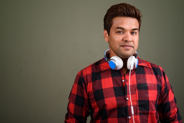 Студийный снимок индийского мужчины в наушниках на цветном фоне