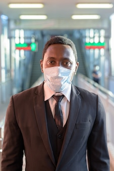 Портрет африканского бизнесмена с маской на вокзале на открытом воздухе