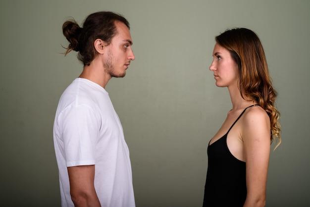 若いハンサムな男と色付きの背景に対して一緒に若い美しい女性のスタジオ撮影