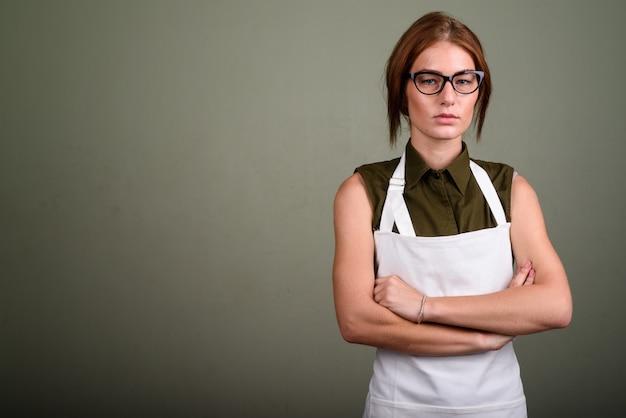 色付きの背景に対してエプロンと眼鏡を着ている若い女性のスタジオ撮影