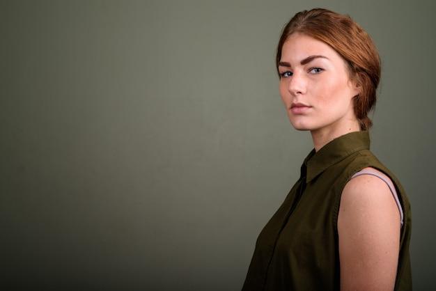 色付きの背景に緑のノースリーブトップを着ている若い女性のスタジオ撮影