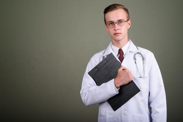 色付きの背景に対してクリップボードを押しながら眼鏡をかけている若いハンサムな男医師のスタジオ撮影