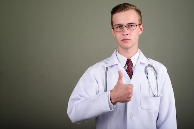 色付きの背景に対して眼鏡を着ている若いハンサムな男医師のスタジオ撮影