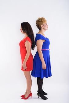 全身ショットシニアアジア女性と白い背景に背中合わせに立っている若い美しい女性の縦断ビュー