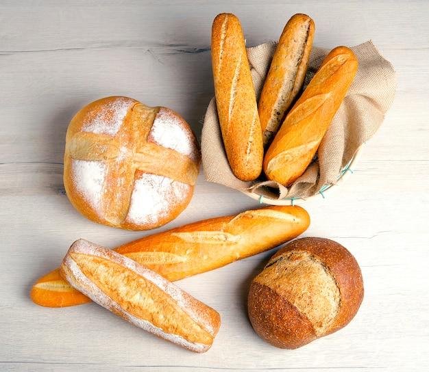Разнообразие хлебов на деревянном столе. вид сверху