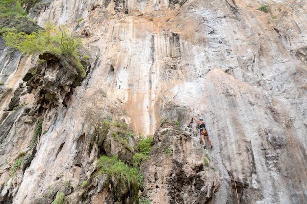 観光客はライレイ湾、クラビで崖を登っています。