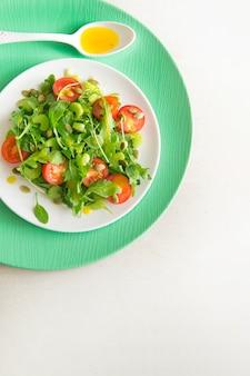 ルッコラ、チェリートマト、ひまわりの種、白いセラミックプレート、上面図、コピースペースのベジタリアンサラダ