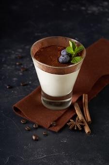 Десерт тирамису в стеклянной чашке с мятой и черникой на темном деревенском столе
