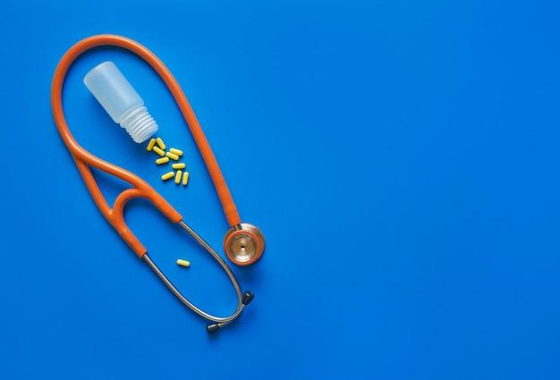 ヘルスケアの概念黄色い錠剤と青いテーブルに聴診器。コピースペースの平面図。