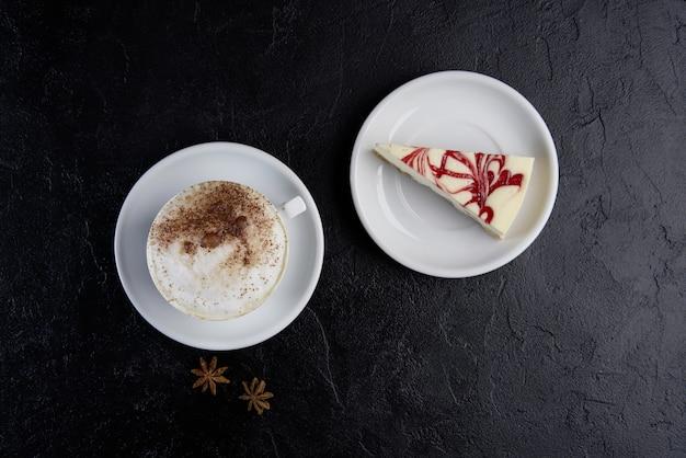 カプチーノコーヒーとチーズケーキのカップ。コピースペース、トップビュー、フラットレイアウト