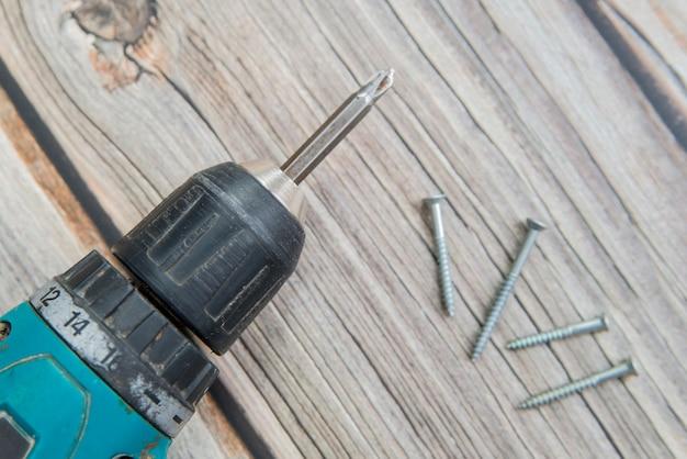 古いドライバーとネジは木製の背景の上に敷設します。電動ドライバーの平面図