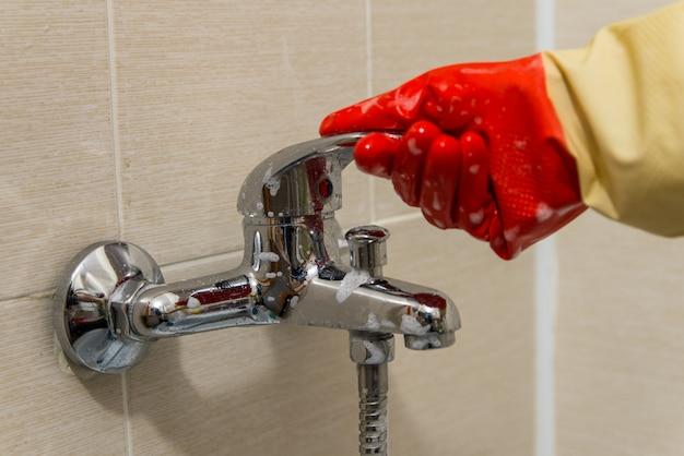 ゴム手袋で手を汚れた石灰化シャワーミキサータップをきれいにし、写真をクローズアップ