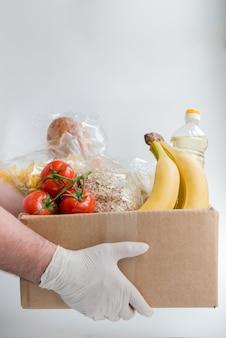 Человек в резиновых перчатках держит коробку с едой