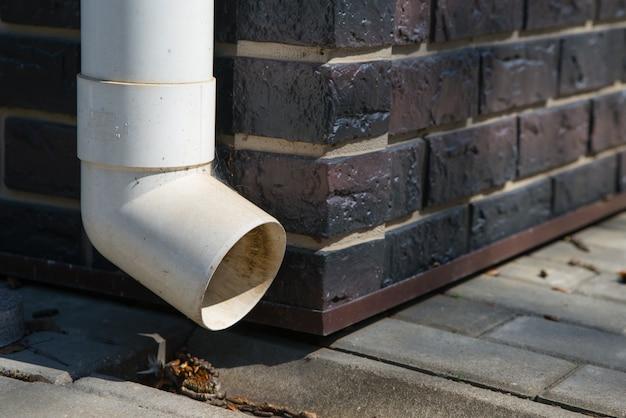 茶色のレンガの壁に古い白いプラスチック排水管。ダウンスパウト