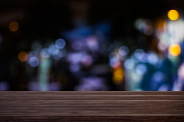 ぼやけている軽い金のボケ味を持つ木製のテーブルの空のカフェレストランやコーヒーショップをぼかし