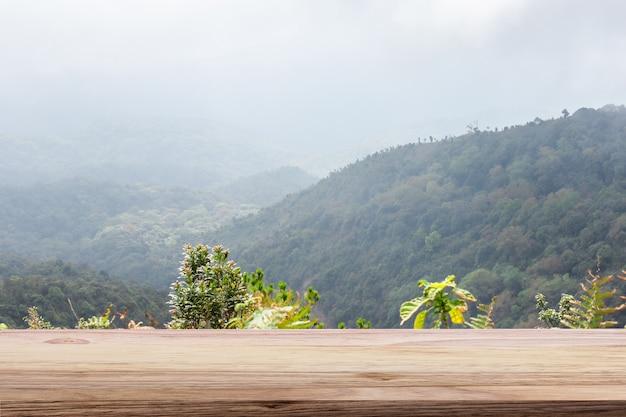 木製のテーブルライトブラウン色の山と霧の背景。モンタージュ商品展示用。