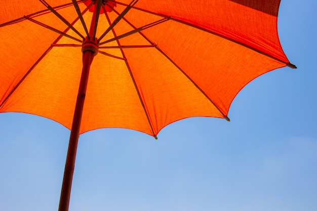 オレンジ色のビーチパラソルは明るい青空を背景にした保護された日光のために木製で作られています。