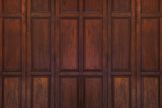 ダークブラウンの古い古代の木製スイングドアの背景。タイの伝統的なスタイル。壁や壁紙として使う。