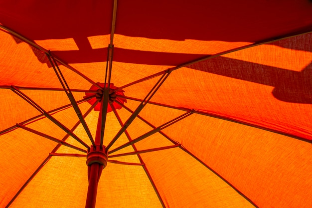 保護された日光のために木で作られたオレンジ色のビーチパラソルの構造をクローズアップ。