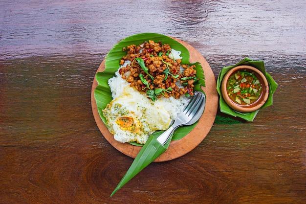 Рис с обжаренным фаршем из свинины и базиликом с яичницей.