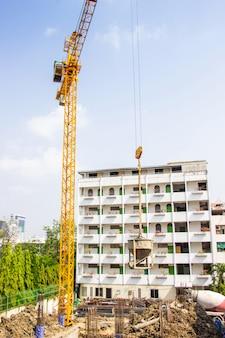 Кран используется при возведении высоких зданий для инструмента крупной промышленности под голубым небом и белыми облаками.