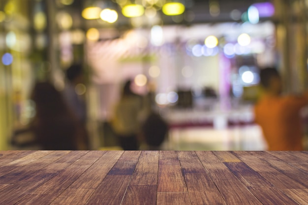 カフェレストランやコーヒーショップは、ぼやけた光金ボケ抽象的な背景と暗い木製のテーブルの空をぼかします。