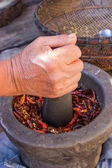 女性の手は唐辛子とニンニクを粉砕しています