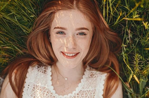 Крупным планом портрет жизнерадостной подростковой женщины отдыхает на траве