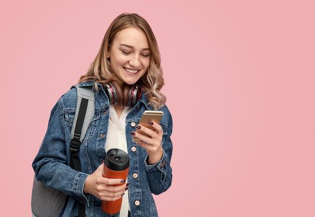 スマートフォンを使用して魔法瓶と陽気な学生
