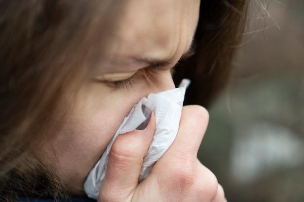 Больная молодая кавказская дама сморкается в носовом платке, стоя на улице в холодную погоду.