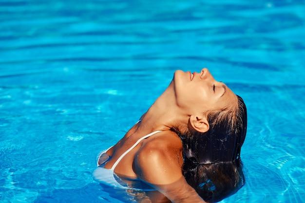ビキニでセクシーな美しい女性モデルはスイミングプールでリラックス