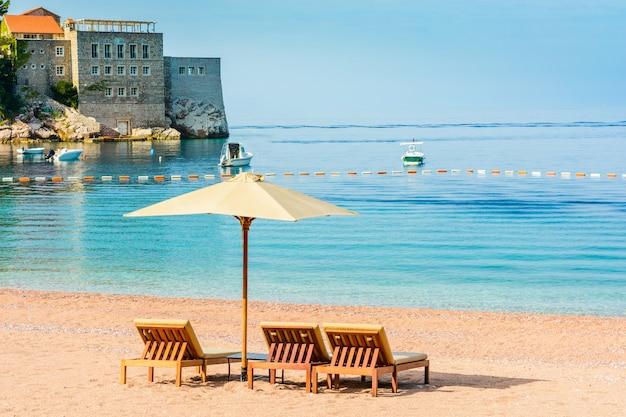 Красивый пляж с навесами в черногории, балканах, адриатическом море.