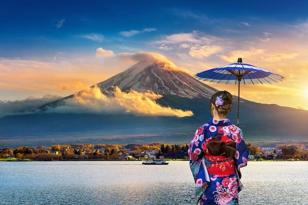 Азиатская женщина нося японское традиционное кимоно на горе фудзи.