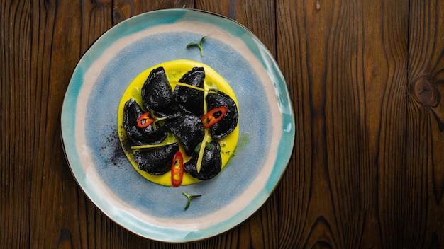 木製のテーブルにシーフードと黒のラビオリ