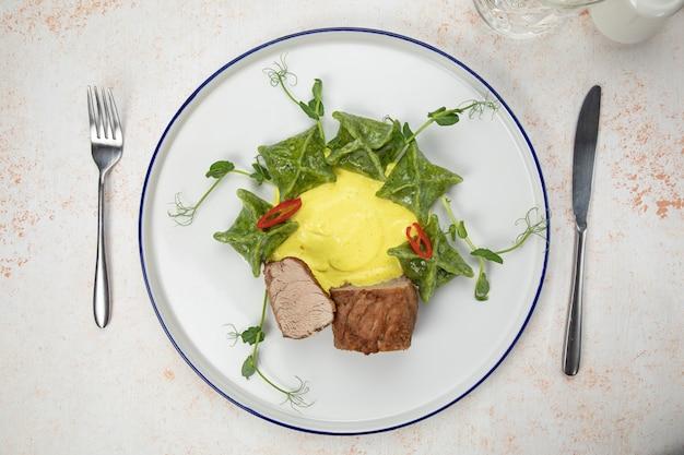 肉とソースのかけらと黄色のラビオリ。白いテーブルの上