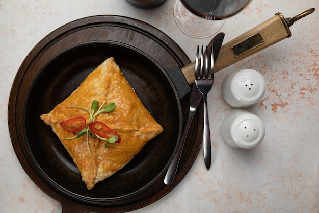 ひき肉と玉ねぎを白いテーブルに黒いセラミック鍋に詰めて揚げた回転のクローズアップ