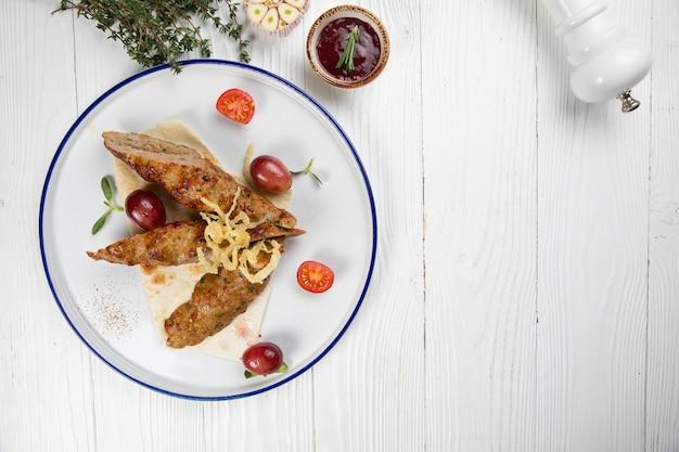 木製の背景にニンニクとピタパンの肉